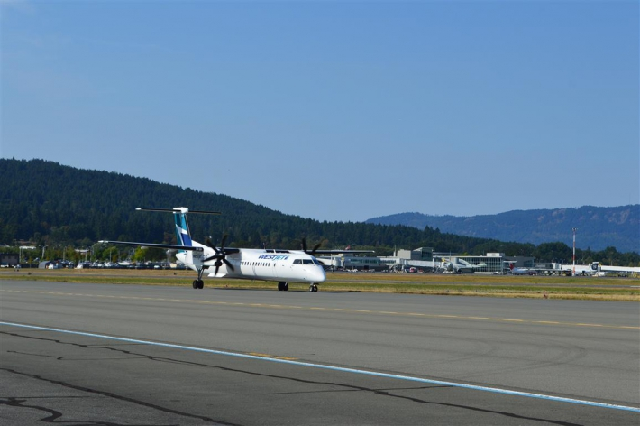 August - WestJet Encore Q400 taxis past Apron III on taxiway Sierra to Runway 27.