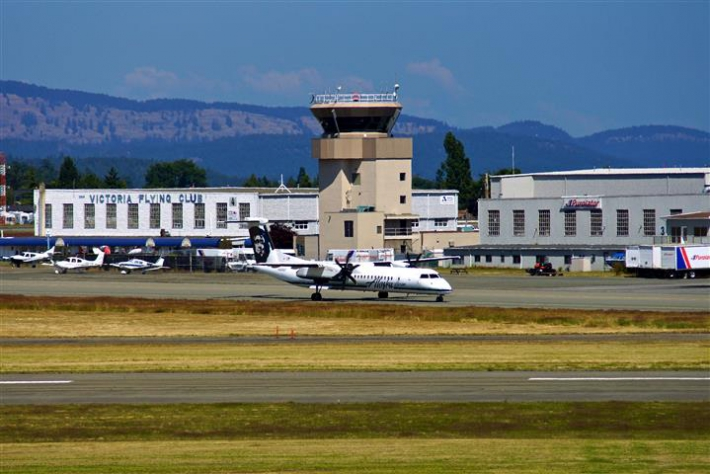 Alaska Airlines Q400t taxis by Victoria Flying Club and Air Traffic Control Tower July 2013