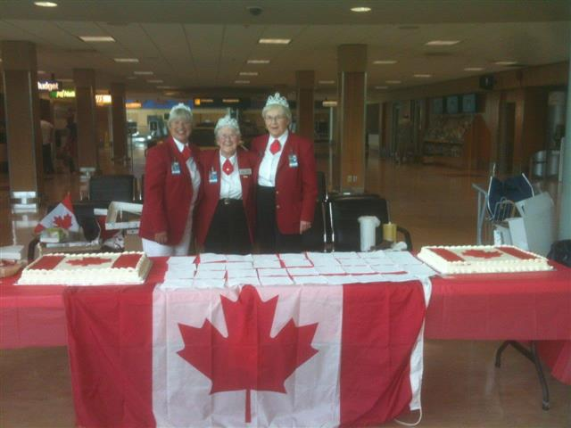 July - Red Coats Margarete, Doreen and Jacqueline serving Canada Day cake.